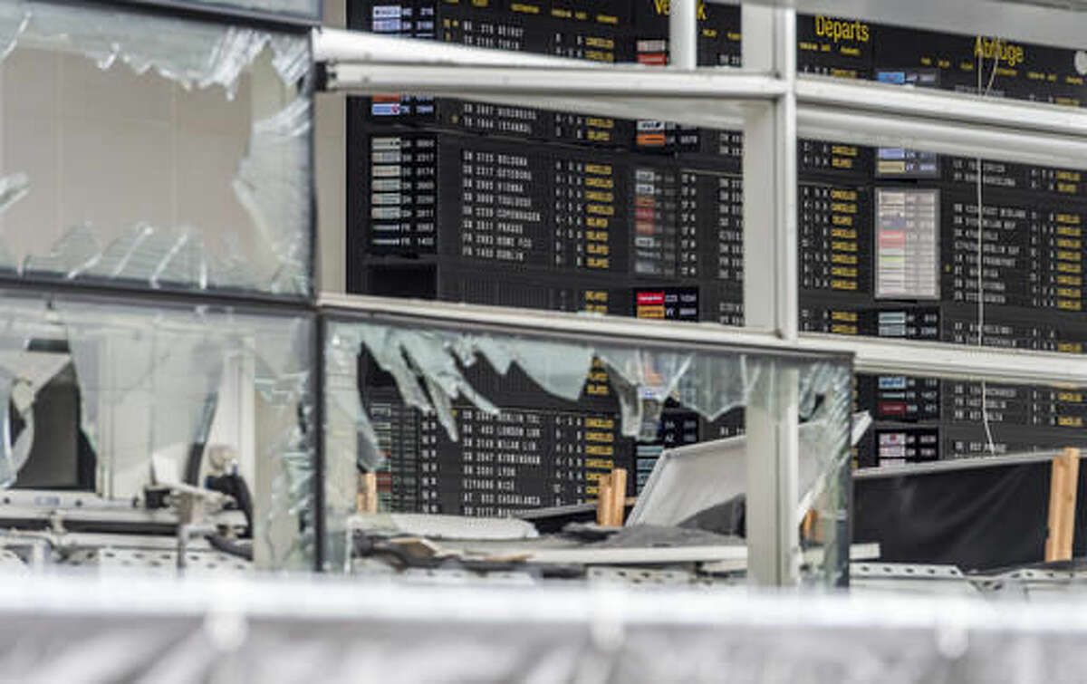 FILE - In this March 23, 2016 file photo, an arrivals and departure board is seen behind blown out windows at Zaventem Airport in Brussels. The European Union on Wednesday, Nov. 16, 2016 unveiled plans for a new system of security checks on travelers permitted to enter Europe without visas in an effort to crack down on extremists. (AP Photo/Geert Vanden Wijngaert, File)