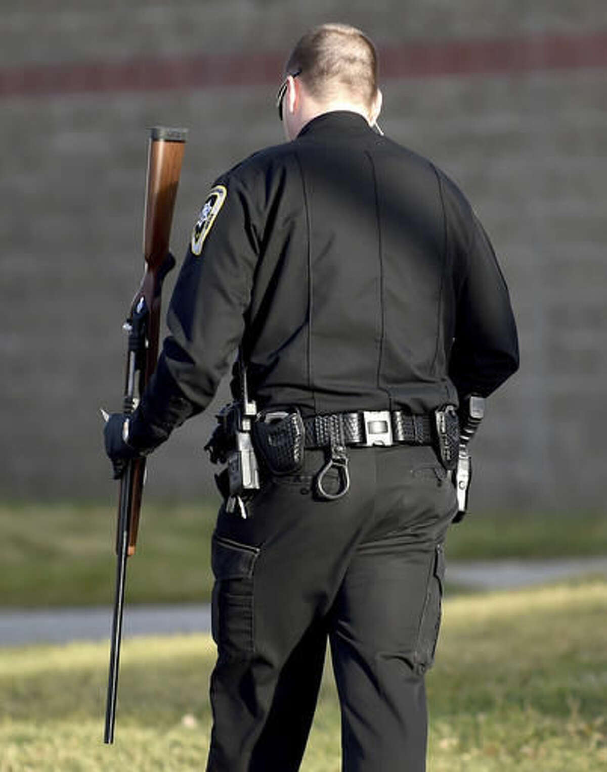 A Yellowstone County Sheriff's Deputy holds a rifle walking from the Montana Pavilion to his patrol car on Friday afternoon, Nov. 25, 2016, in Billings, Mont. Authorities say a bolt-action rifle was fired during a gun show in Billings, injuring a man and a young girl. Capt. Bill Michaelis of the Yellowstone County Sheriff's Office told the Billings Gazette that a vendor was showing the gun to somebody when it discharged Friday. (Hannah Potes/The Billings Gazette via AP)