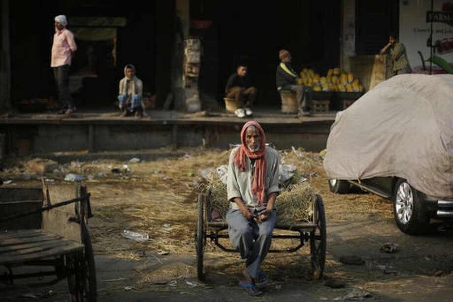 """In this Friday, Nov. 18, 2016 photo, a laborer sits on his cart waiting for work at Azadpur Mandi, one of Asia's largest wholesale market for fruits and vegetables in New Delhi, India. Business at the massive New Delhi market is evaporating, the food spoiling and wasted, two weeks after the government's surprise currency move made more than 80 percent of India's banknotes useless. By withdrawing all 500- and 1,000-rupee notes from circulation, the government is trying to clean India's economy of """"black money,"""" or untaxed wealth. Its success remains to be seen, but for now the move has created serpentine queues outsides banks and ATMs of people replacing their rupee notes or making small withdrawals. (AP Photo/Altaf Qadri) Photo: Altaf Qadri"""