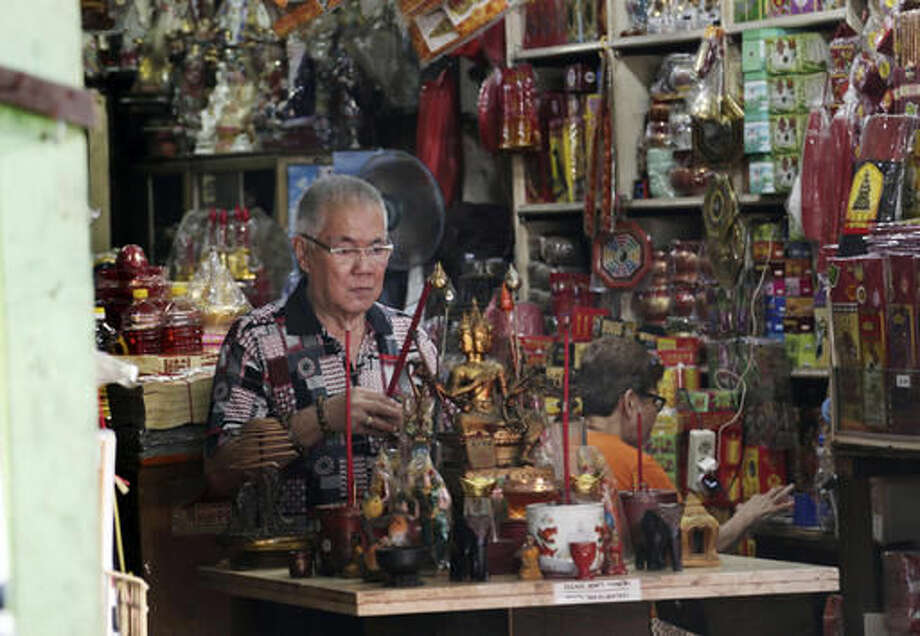 In this Monday, Nov. 28, 2016 photo, Indonesian ethnic Chinese Jhony Tan prays at his store at the Chinatown in Jakarta, Indonesia. The capital of Muslim-majority Indonesia is on edge ahead of what is expected to be a second massive protest on Friday by conservative Muslims against its Christian governor and no group more so than its Chinese minority. They have reason to be concerned. The movement against the governor, who is being prosecuted for allegedly insulting the Quran, has overflowed with racial slurs against his Chinese ancestry and has awakened painful memories of deadly anti-Chinese riots in 1998. (AP Photo/Achmad Ibrahim) Photo: Achmad Ibrahim