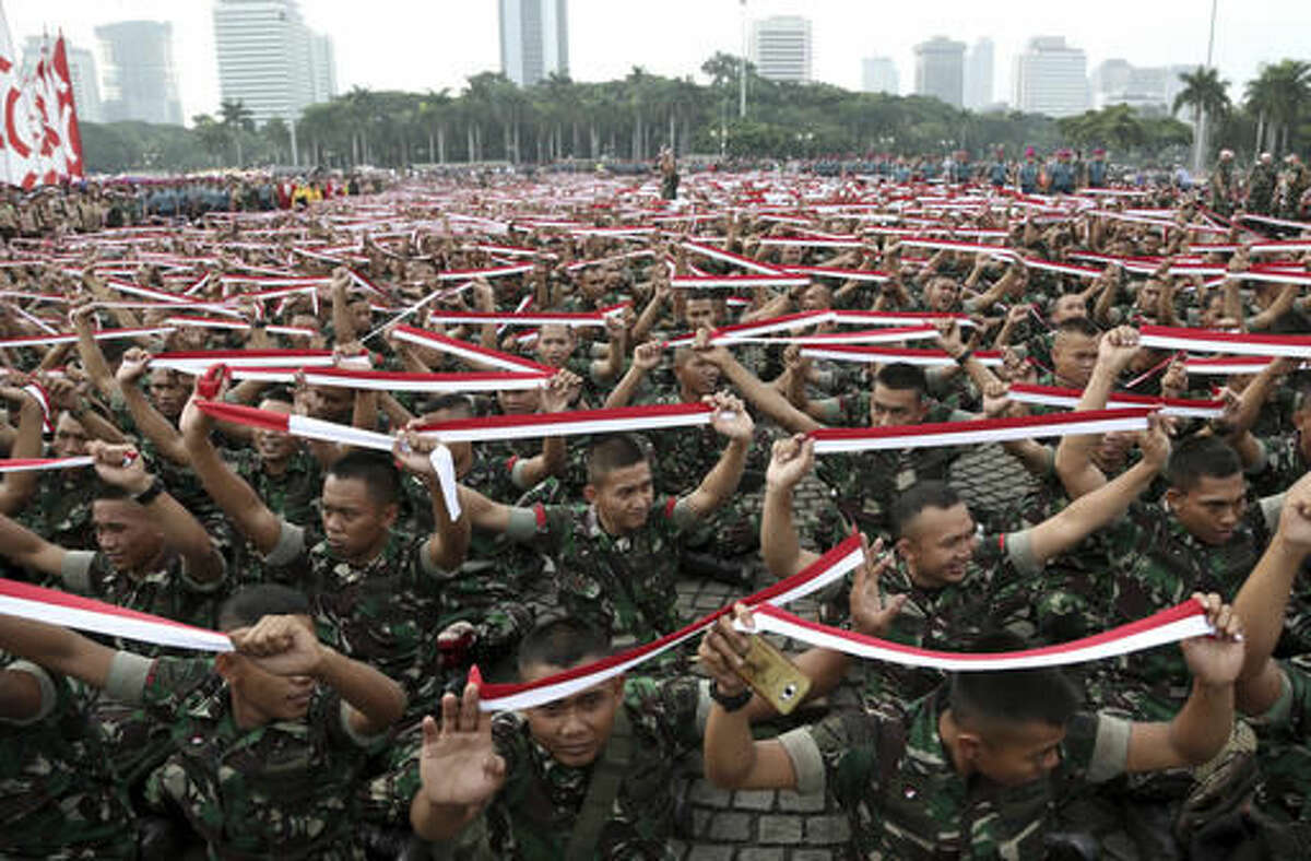 Indonesian soldiers hold up headbands in the color of the national Red-White flag during a military-sponsored interfaith rally held ahead of the planned Dec. 2 Muslim rally against Jakarta Governor Basuki Tjahaja Purnama in Jakarta, Indonesia, Wednesday, Nov. 30, 2016. The capital of Muslim-majority Indonesia is on edge ahead of what is expected to be a second massive protest by conservative Muslims against its Christian ethnic Chinese governor. (AP Photo/Achmad Ibrahim)