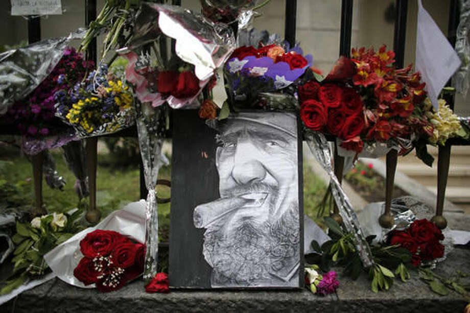 A caricature depicting Cuba's late leader Fidel Castro is surrounded by flowers at a makeshift memorial outside the Cuban embassy in Buenos Aires, Argentina, Monday, Nov. 28, 2016. Castro, who led a rebel army to improbable victory, embraced Soviet-style communism and defied the power of 10 U.S. presidents during his half century rule of Cuba, died late Friday at age 90. (AP Photo/Victor R. Caivano) Photo: Victor R. Caivano