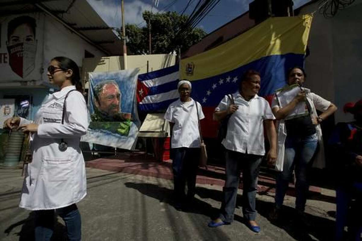 Cuban doctors working in Venezuela wait for pacients outside their clinic, where an image of Fidel Castro and a Cuban and Venezuelan flag hangs, in the 23 de Enero neighborhood in Caracas, Venezuela, Saturday, Nov. 26, 2016, the day after Castro's death. Castro, who led a rebel army to improbable victory, embraced Soviet-style communism and defied the power of 10 U.S. presidents during his half century rule of Cuba, died at age 90 in Cuba late Friday, Nov. 25. (AP Photo/Fernando Llano)