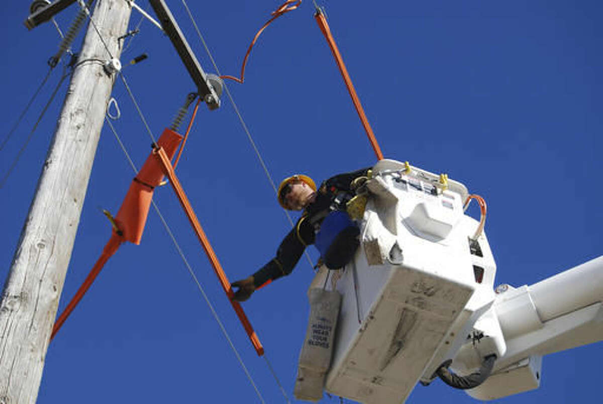 In this Nov. 11, 2016 photo, Idaho Power Co. apprentice lineman Claysen Hale prepares to change out jumpers and stirrups on a power line in Eden, Idaho. The company's apprenticeship programs, implemented in 1954, have helped to address the need for skilled employees, decrease turnover and replace retired workers. (Heather Kennison/Times-News via AP)
