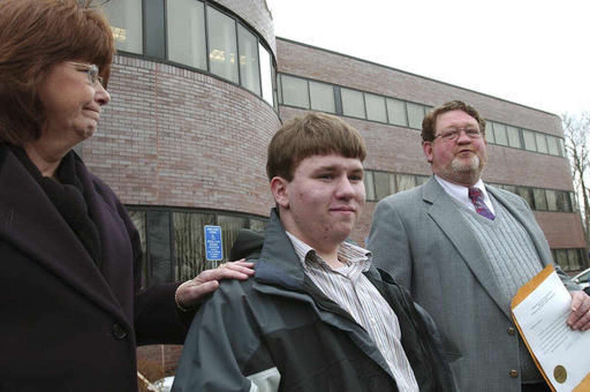 """FILE - In the March 24, 2005 file photo Patrick Holland, center, stands with his adoptive parents Rita and Ron Lazisky after his adoption was finalized at the Norfolk County Probate Court in Canton, Mass. Holland, 15, was granted a ground-breaking """"divorce"""" from his birth father, Daniel Holland, last summer following his conviction in the murder of Patrick's birth mother. A murder case that prompted Patrick Holland to seek a """"divorce"""" from his father is going before Massachusetts' top court 18 years after the killing. The state Supreme Judicial Court is scheduled to hear arguments Thursday, Nov. 10, 2016. (AP Photo/Neal Hamberg, File)"""