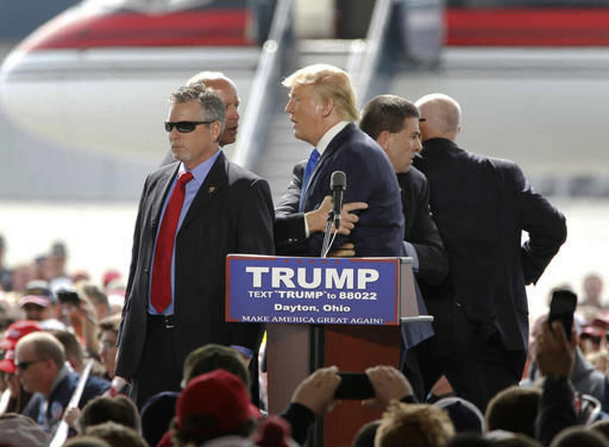 FILE - In this March 12, 2016, file photo, security personnel surround Republican presidential candidate Donald Trump after a man rushed the stage during a campaign rally at the Wright Brothers Aero Hangar at Dayton International Airport in Vandalia, Ohio. With the election over, a federal judge has ended probation for an Ohio man who tried to rush a Donald Trump rally stage. Judge Sharon Ovington's Thursday, Nov. 17, order says she cut short a scheduled, one-year probation for DiMassimo based on his probation officer's recommendation and without objection from the U.S. attorney's office. (Lisa Powell/Dayton Daily News via AP, File)