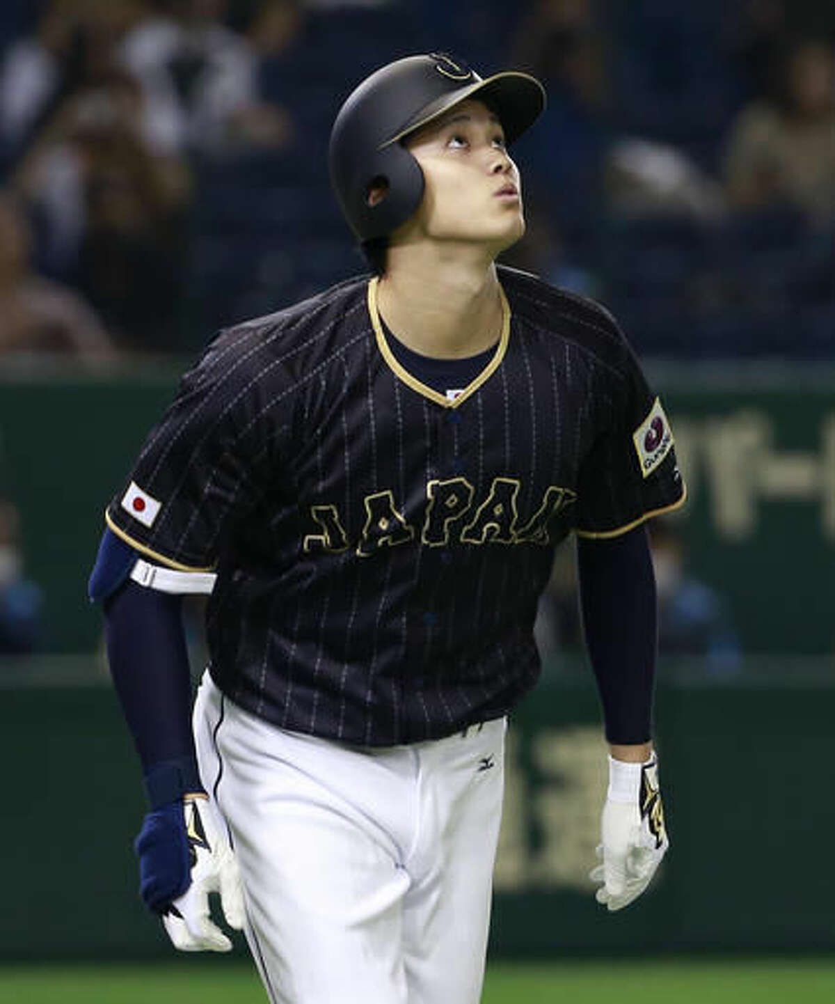 Japan's pinch hitter Shohei Otani watches the flight of his ground-rule double against the Netherlands in the seventh inning of their international exhibition series baseball game at Tokyo Dome in Tokyo, Sunday, Nov. 13, 2016. (AP Photo/Shizuo Kambayashi)