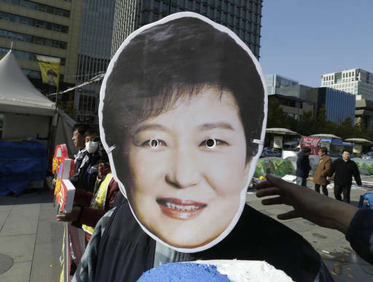 A South Korean protester wears a mask of South Korean President Park Geun-hye during a rally calling for Park to step down in downtown Seoul, South Korea, Friday, Nov. 11, 2016. Tens of thousands of South Koreans are expected to march in Seoul to demand Park's resignation on Saturday over a snowballing influence-peddling scandal involving Park's longtime confidante. (AP Photo/Ahn Young-joon)