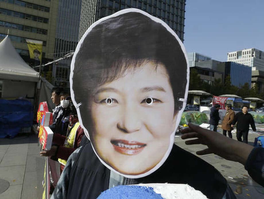 A South Korean protester wears a mask of South Korean President Park Geun-hye during a rally calling for Park to step down in downtown Seoul, South Korea, Friday, Nov. 11, 2016. Tens of thousands of South Koreans are expected to march in Seoul to demand Park's resignation on Saturday over a snowballing influence-peddling scandal involving Park's longtime confidante. (AP Photo/Ahn Young-joon) Photo: Ahn Young-joon