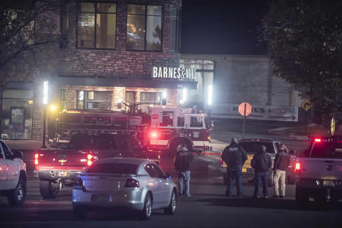 In this Saturday, Nov. 26, 2016, photo, Albuquerque firefighters respond to a fire set inside the Barnes & Noble bookstore in Albuquerque, N.M. Federal authorities charged a man on Monday, Nov. 28, with using an explosive device to damage an Old Navy store in Albuquerque, where a string of local, overnight fires and instances of vandalism during the busiest shopping weekend of the year damaged three Starbucks shops, a Barnes & Noble, and other establishments in New Mexico's largest city. (Roberto Rosales/The Albuquerque Journal via AP)
