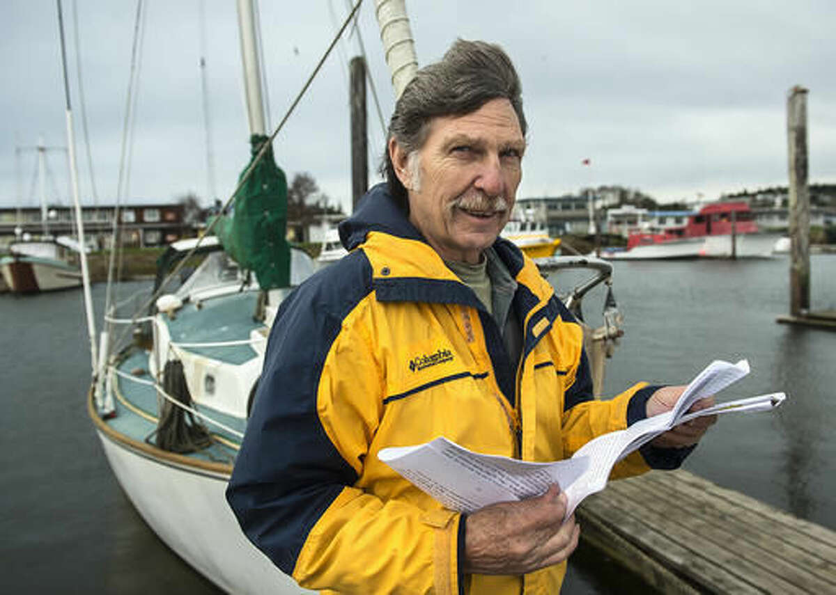 """In this Nov. 18, 2016 photo, Desmond Doss, Jr. holds correspondence about his father, the subject of the film, """"Hacksaw Ridge,"""" while on a dock in Ilwaco, Wash. Doss Jr., has been flooded with emails and letters regarding his father, a World War II soldier who refused to touch a gun and who single-handedly rescued 75 wounded soldiers. (Bill Wagner/The Daily News via AP)"""