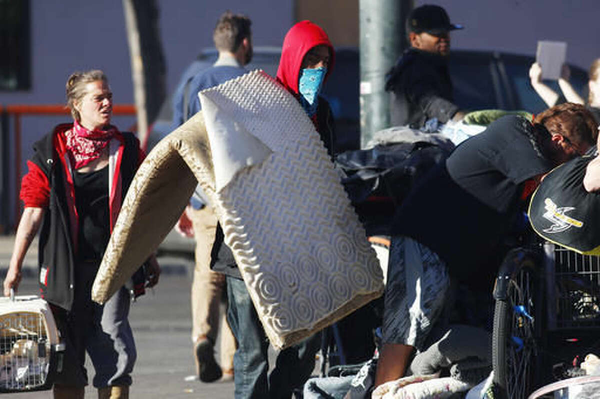 An unidentified man carries his belongings during a sweep of homeless people who were living on the walks surrounding a shelter near the baseball stadium Tuesday, Nov. 15, 2016, in downtown Denver. A new report from The National Law Center on Homelessness and Poverty said Tuesday, Nov. 15, 2016, that cities nationwide such as Denver are enacting more policies that criminalize homelessness. (AP Photo/David Zalubowski)