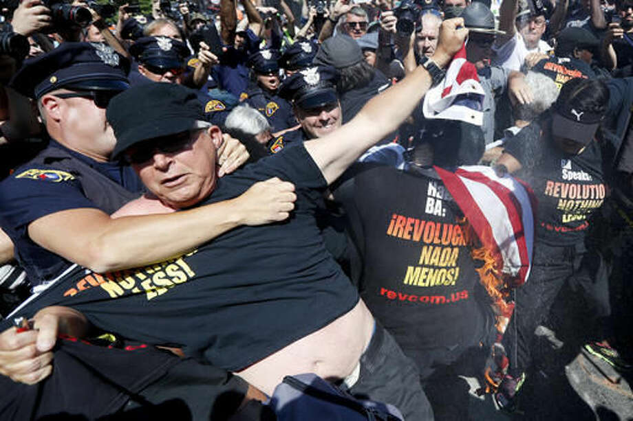 """FILE - In this July 20, 2016 file photo, a law enforcement officer takes Gregory Johnson into custody after he started to burn an American flag in Cleveland, during the third day of the Republican convention. President-elect Donald Trump said Tuesday that anyone who burns an American flag should face unspecified """"consequences,"""" such as jail or a loss of citizenship _ a move that was ruled out by the Supreme Court nearly three decades ago. (AP Photo/John Minchillo) Photo: John Minchillo"""