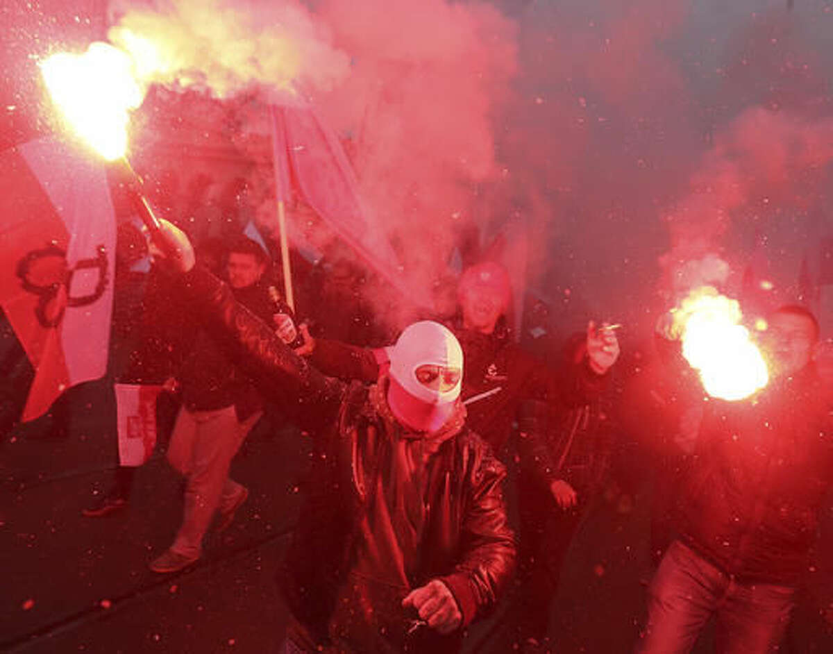 Nationalists, burning flares as they march in large numbers through the streets of Warsaw to mark Poland's Independence Day in Warsaw, Poland, Friday, Nov. 11, 2016. AP Photo/Czarek Sokolowski)