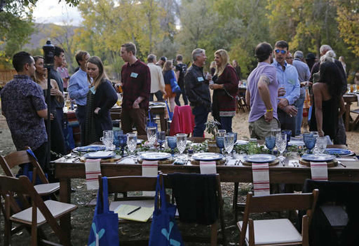 FILE - In this Oct. 2, 2016, file photo, diners chat and smoke marijuana, before eating dishes prepared by chefs during an evening of pairings of fine food and craft marijuana strains served to invited guests dining at Planet Bluegrass, an outdoor venue in Lyons, Colo. Opponents of a state ruling that would prevent bars and many restaurants in Denver from offering on-site marijuana consumption said the ruling would overturn a law approved by voters and force people to sneak around while they use pot and consume alcohol. The new rule announced Friday, Nov. 18 by the Liquor Enforcement Division of the Colorado Department of Revenue bars liquor-license holders from applying for a permit to allow the consumption of pot. (AP Photo/Brennan Linsley, File)