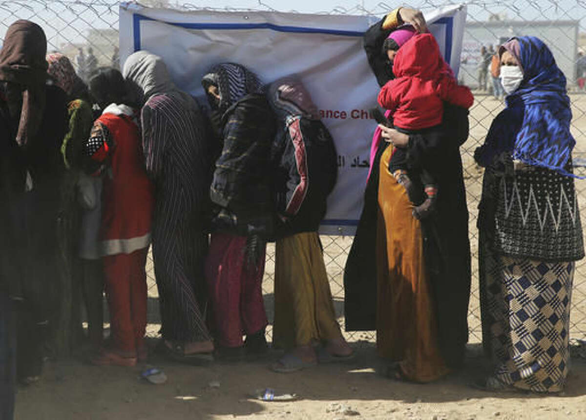 Iraqi citizens who fled the fighting between Islamic State militants and the Iraqi forces, line up to receive aid supplies, at a camp for internally displaced people, in Khazer, east of Mosul, Iraq, Monday, Nov. 21, 2016. Iraqi troops fighting Islamic State militants in the eastern outskirts of Mosul regrouped Monday in the city's neighborhoods they recently retook from the extremist group, conducting house-to-house searches and looking for would-be suicide car bombs, a top Iraqi commander said. (AP Photo/Hussein Malla)
