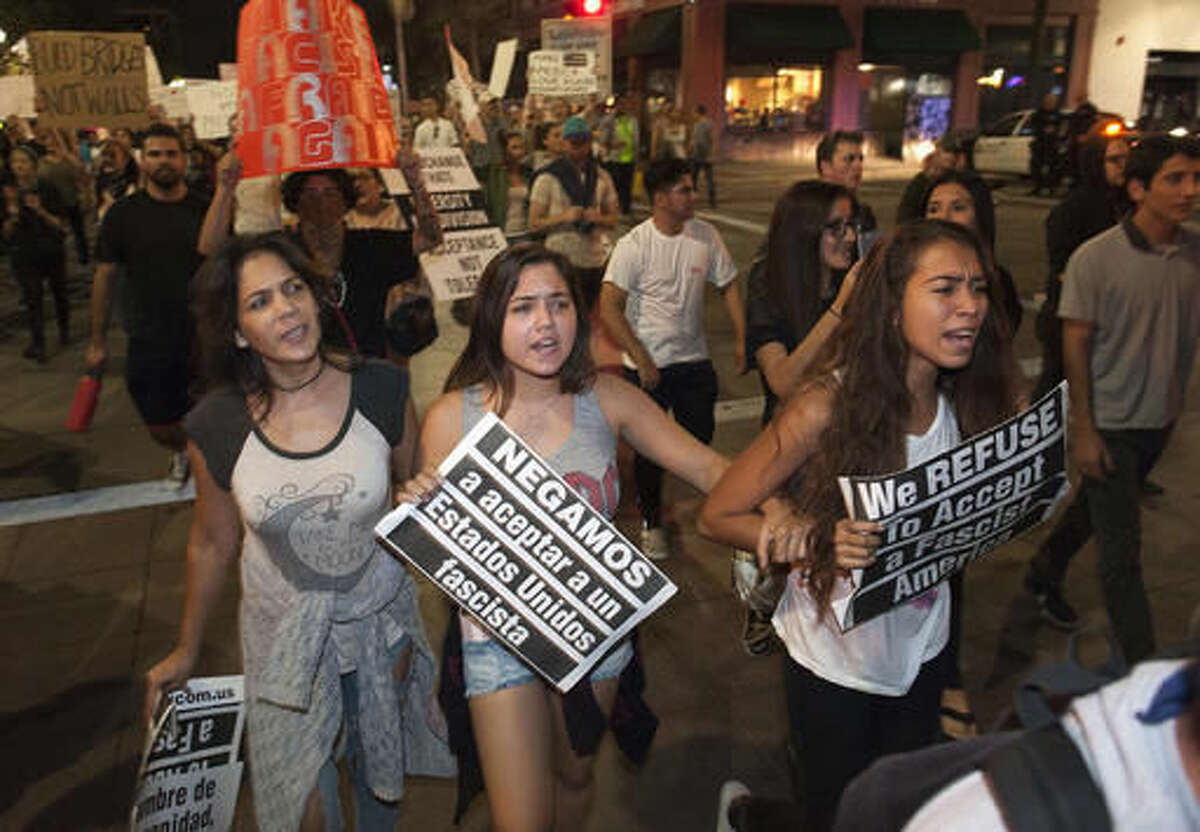 """Protesters walk a street during an anti-Trump protest downtown Santa Ana, Calif., Sunday, Nov. 13, 2016. The sign, center, reads, """"We refuse to accept a fascist United States."""" (Ana Venegas/The Orange County Register via AP)"""