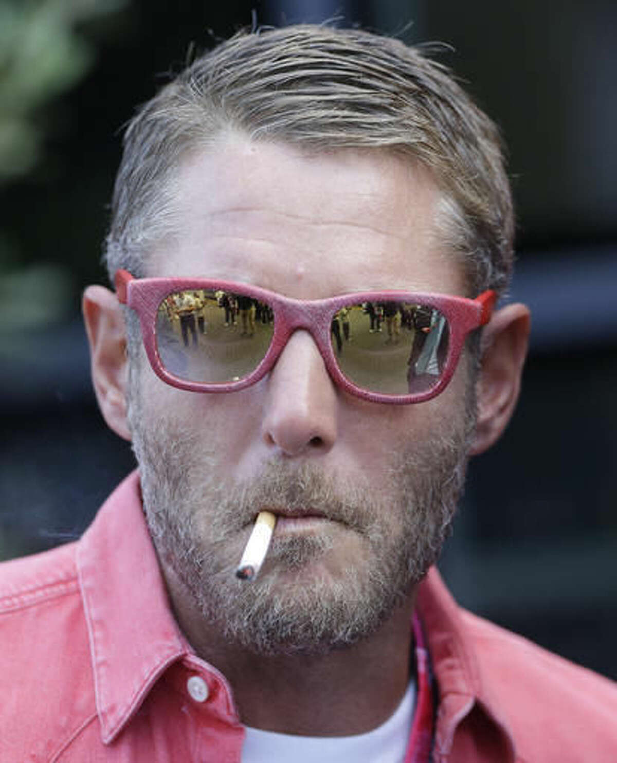 FILE- In this Sept. 5, 2015 file photo, Italian entrepreneur Lapo Elkann smokes prior to the start of the third practice session for Sunday's Formula One Italian Grand Prix, at the Monza racetrack, Italy. Police in New York City say the grandson of the Italian founder of Fiat Automobiles was arrested on Saturday, Nov. 26, 2016, after falsely claiming an escort held him against his will. (AP Photo/Luca Bruno, File)