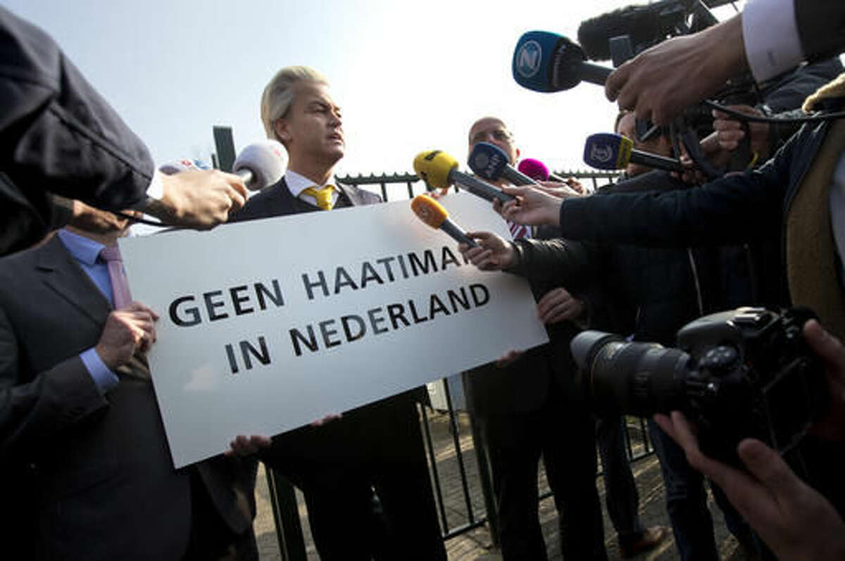 """FILE - In this Thursday, April 9, 2015 file photo Geert Wilders, leader of the anti-Islam Freedom Party, holds a sign reading """"No Hate Imams in the Netherlands"""" in Utrecht, central Netherlands. Dutch prosecutors have begun summing up their case against populist anti-Islam lawmaker Geert Wilders in his hate-speech trial that pits freedom of expression against the Netherlands' anti-discrimination laws. (AP Photo/Peter Dejong, File)"""