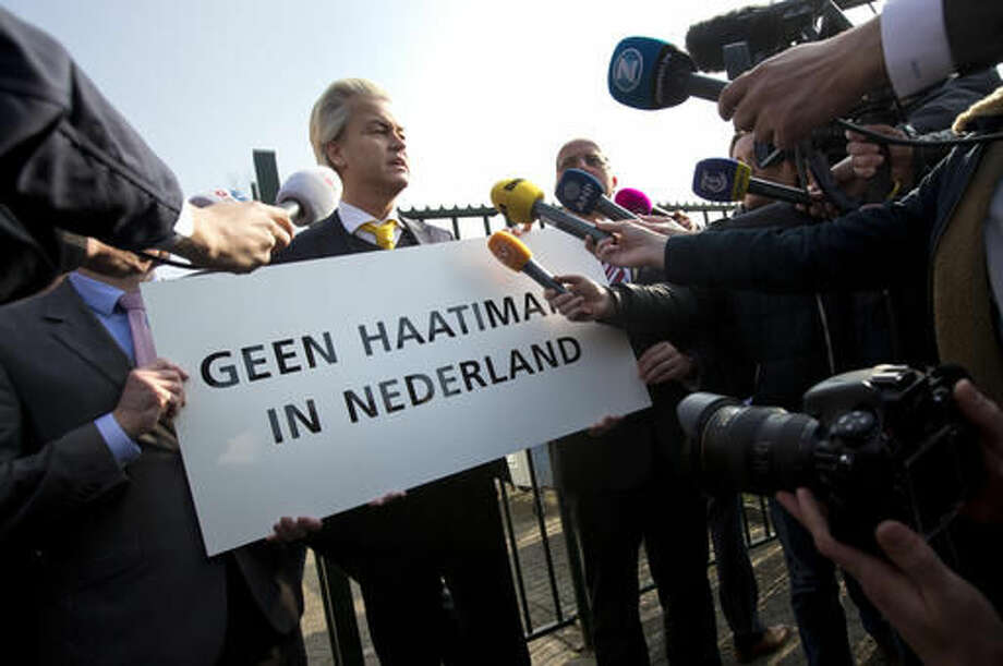 """FILE - In this Thursday, April 9, 2015 file photo Geert Wilders, leader of the anti-Islam Freedom Party, holds a sign reading """"No Hate Imams in the Netherlands"""" in Utrecht, central Netherlands. Dutch prosecutors have begun summing up their case against populist anti-Islam lawmaker Geert Wilders in his hate-speech trial that pits freedom of expression against the Netherlands' anti-discrimination laws. (AP Photo/Peter Dejong, File) Photo: Peter Dejong"""