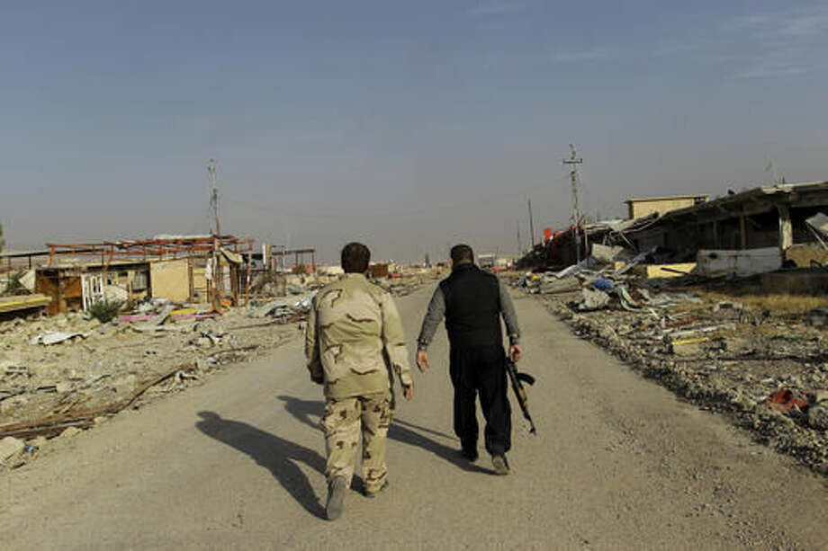 Ali Hussein, right, and his son walk to check on the family's used car business, which was looted by Islamic State fighters and destroyed in fighting to oust them in Bashiqa, east of Mosul, Iraq, Friday, Nov. 11, 2016. Iraqi troops inched ahead in their battle to retake the northern city of Mosul from the Islamic State group on Friday, as the U.N. revealed fresh evidence that the extremists have used chemical weapons. (AP Photo/Adam Schreck) Photo: Adam Schreck