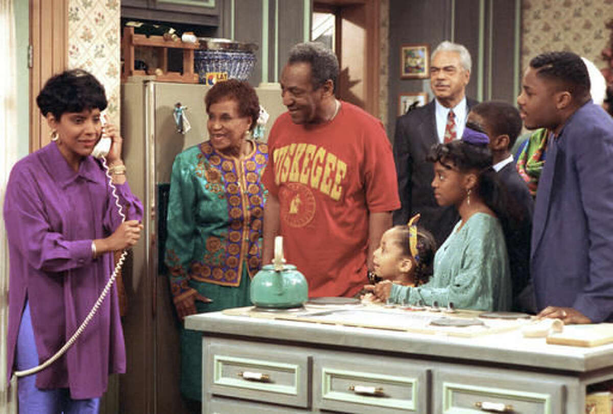 """FILE - In this March 6, 1992, file photo, Phylicia Rashad, as Clair Huxtable, talks on the telephone while Bill Cosby, as Dr. Cliff Huxtable, center, and other cast members of the family sitcom """"The Cosby Show,"""" gather around during taping of the final episode in New York. Bounce TV announced Nov. 11, 2016, that it would resume airing reruns of """"The Cosby Show"""" on Dec. 19. (AP Photo, File)"""