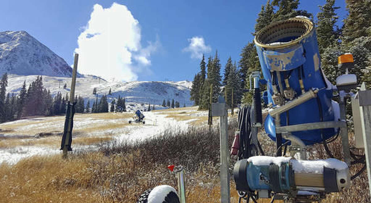 FILE - In this Nov. 2, 2016, file photo, a snowmaking gun sits on an expanse of brown grass near the top of the Black Mountain Express run at Arapahoe Basin Ski Area near Keystone, Colo. Autumn snow has been scarce in the Rocky Mountains, forcing some ski areas to push back opening day and raising concerns about how much water will be available next spring for the Colorado River. But the first big storm of the season is expected to blow into Colorado and Utah on Thursday, Nov. 17, 2016. (Phil Lindeman/Summit Daily News via AP, File)
