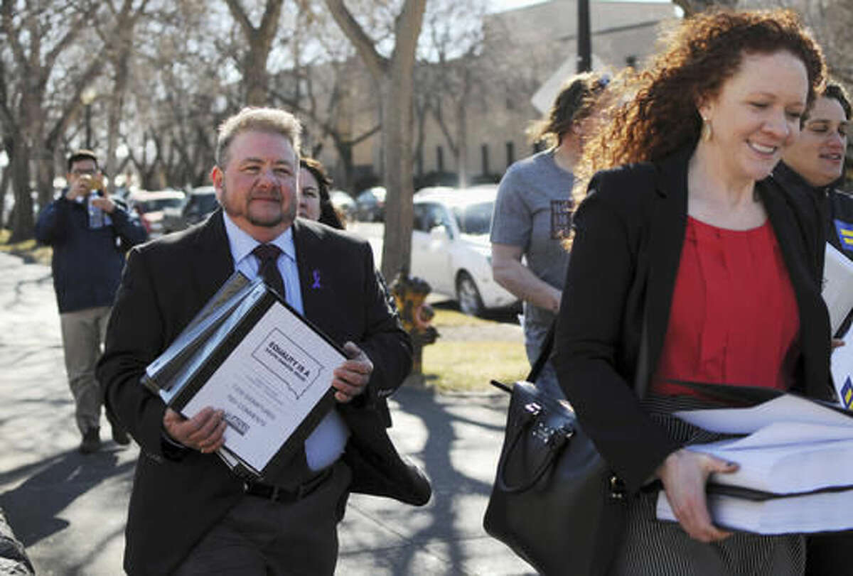 FILE - In this Feb. 23, 2016 file photo, Terri Bruce, left, a transgender man who opposed a bill that South Dakota Gov. Dennis Daugaard vetoed that would have limited the bathrooms that transgender students could use, walks toward the South Dakota state Capitol in Pierre. Bruce said he's disappointed that a ballot measure patterned after the vetoed bill has been proposed and could appear on the 2018 ballot. (AP Photo/James Nord, File)