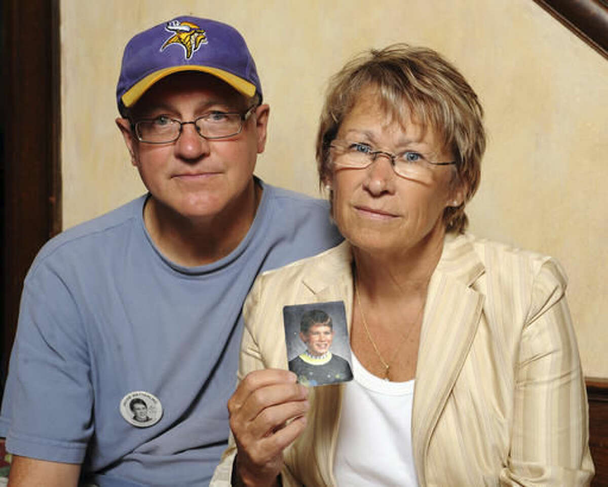 """FILE - In this Aug. 28, 2009 file photo, Patty and Jerry Wetterling show a photo of their son Jacob Wetterling, who was abducted in October 1989 in St. Joseph, Minn and was still missing, in Minneapolis. Daniel Heinrich, of Minnesota, who confessed to kidnapping, sexually assaulting and killing Jacob, has shed """"countless tears"""" for Jacob and his family in the 27 years since his death, his lawyer said in a court filing Thursday, Nov. 17, 2016. Heinrich is scheduled to be sentenced in federal court Monday, Nov. 21 on a child pornography charge that stemmed from the investigation into Jacob's disappearance. As part of his plea deal, prosecutors agreed not to charge him with murder. (AP Photo/Craig Lassig, File)"""
