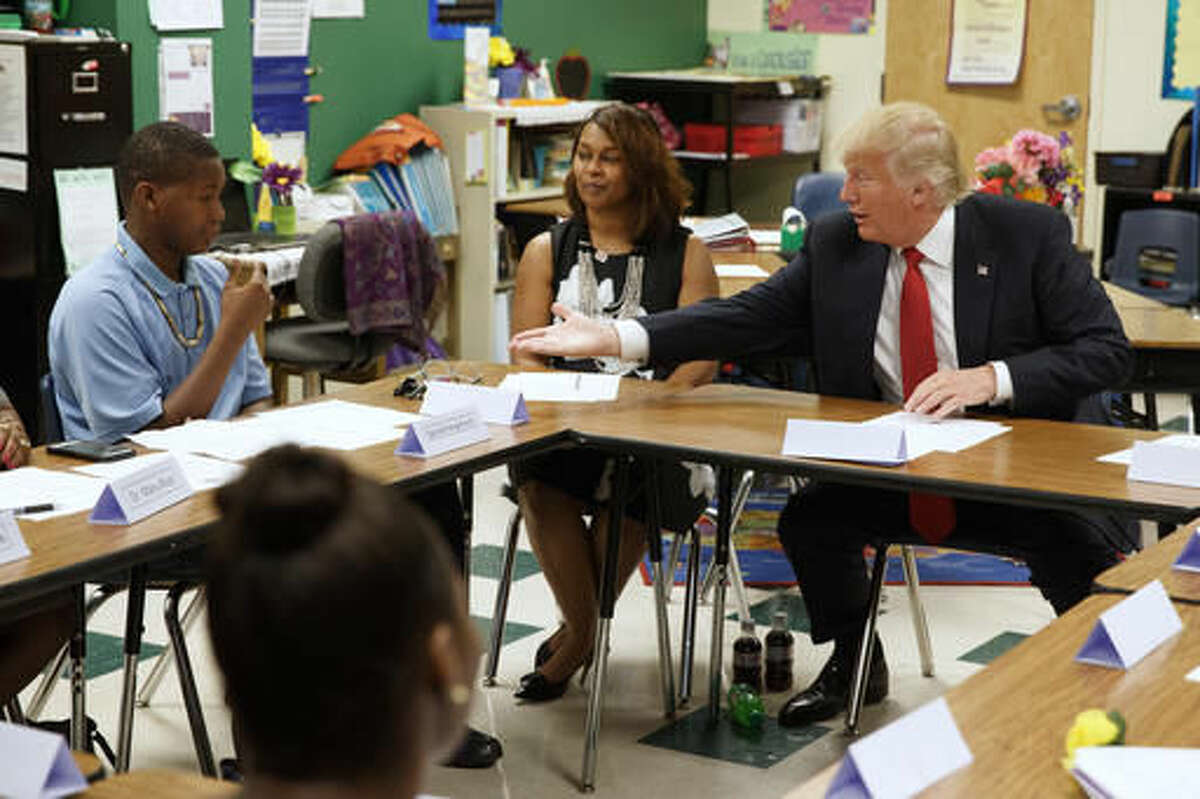 FILE - In this Sept. 8, 2016, file photo, then=Republican presidential candidate Donald Trump reaches to shake hands with Egunjobi Songofunmi during a meeting with students and educators before a speech on school choice at Cleveland Arts and Social Sciences Academy in Cleveland. School voucher programs in the nation's capital and Vice President-elect Mike Pence's home state of Indiana could serve as a blueprint for a Trump administration plan to use public money to enable disadvantaged students to attend the public or private school of their choice. Trump made clear that school choice would be an education priority. (AP Photo/Evan Vucci, File)