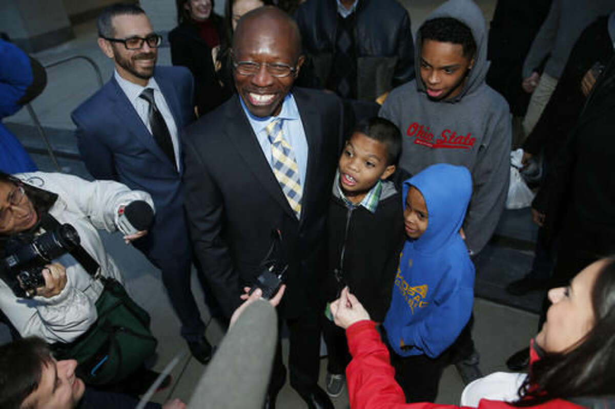 """FILE - In this Dec. 22, 2015, file photo, Clarence Moses-EL, center, hugs three of his grandchildren after his release from the Denver County jail in Denver. Moses-EL, released from prison last year after spending more than a quarter of a century in prison for a rape he long denied committing, was acquitted of the crime on Monday, Nov. 14, 2016, leaving a courtroom to applause from supporters and chants of """"it's over."""" (AP Photo/David Zalubowski, File)"""