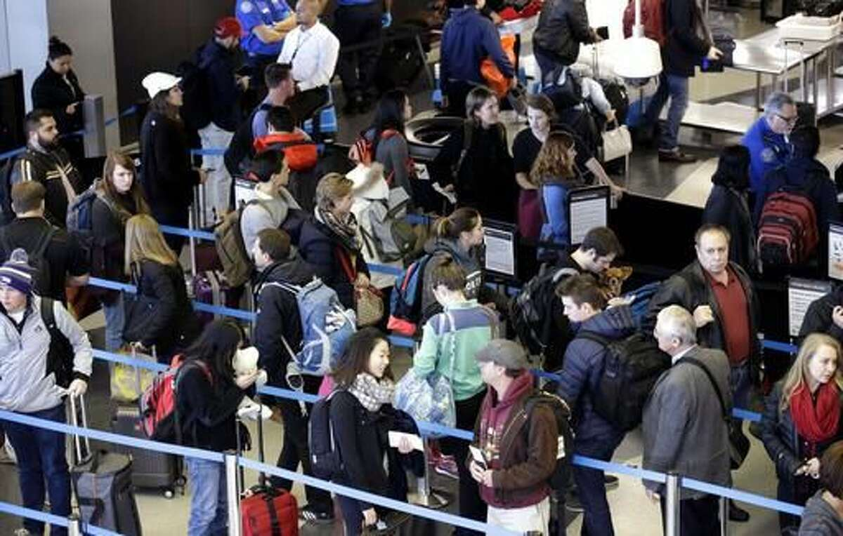 FILE - In this Sunday, Nov. 29, 2015, file photo, travelers line up at a security checkpoint area in Terminal 3 at O'Hare International Airport in Chicago. The auto club AAA said Tuesday, Nov. 15, 2016, that it expects 1 million more Americans to venture at least 50 miles from home, a 1.9 percent increase over last year. (AP Photo/Nam Y. Huh, File)