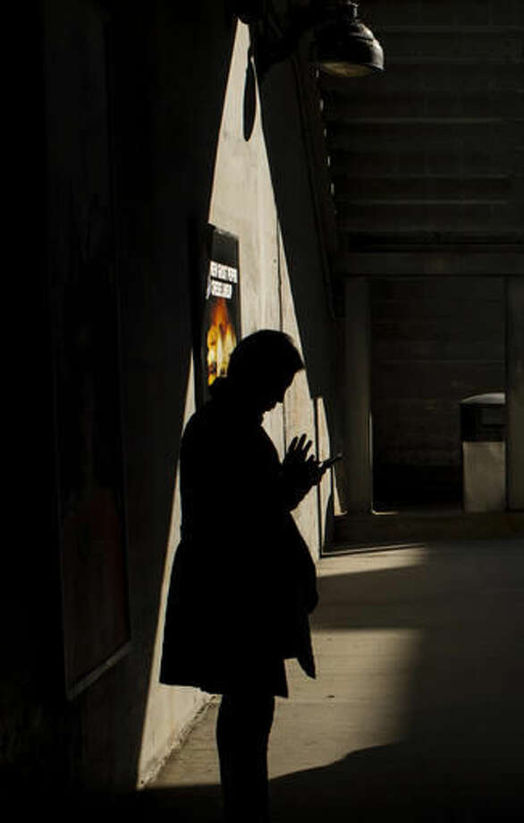 FILE - In this Wednesday, Oct. 12, 2016, file photo, moments before boarding an arriving train to Manhattan, a morning commuter uses his smartphone on the platform of the Long Island Rail Road at the Bayside Station in the Queens borough of New York. TVs are so last century. News outlets are using Facebook Live, Snapchat, YouTube and other tools to offer live coverage of Election Day in ways not possible four years ago. (AP Photo/Alexander F. Yuan, File) Photo: Alexander F. Yuan