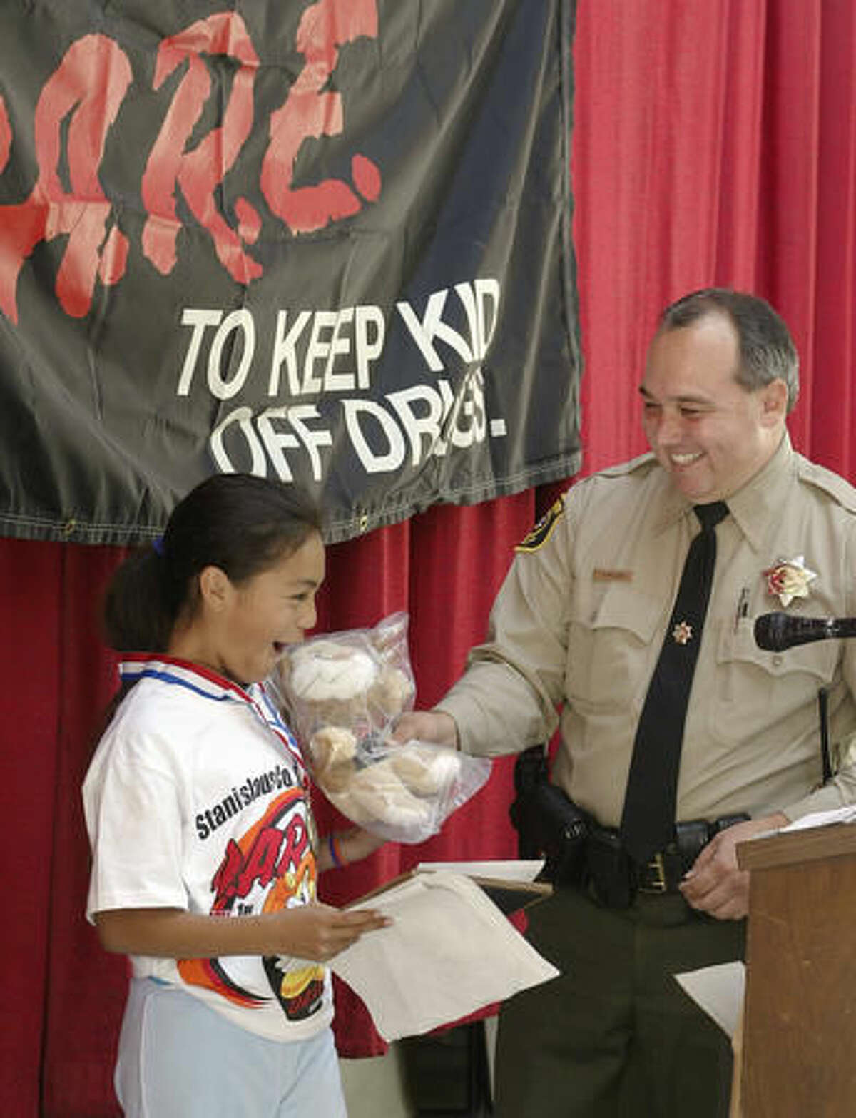 FILE - In this April 30, 2004, file photo, Stanislaus County Sheriff's Deputy Dennis Wallace gives an award to Karissa Toves during Hart Ransom School's graduation program for the DARE program in Modesto, Calif. Wallace, a 20-year-veteran, was fatally shot at point-blank range Sunday, Nov. 13, 2016, as he checked on a report of a suspicious van parked near a fishing access spot outside the city of Hughson, about 10 miles southeast of Modesto, Stanislaus County Sheriff Adam Christianson said. (Marty Bicek/The Modesto Bee via AP, File)