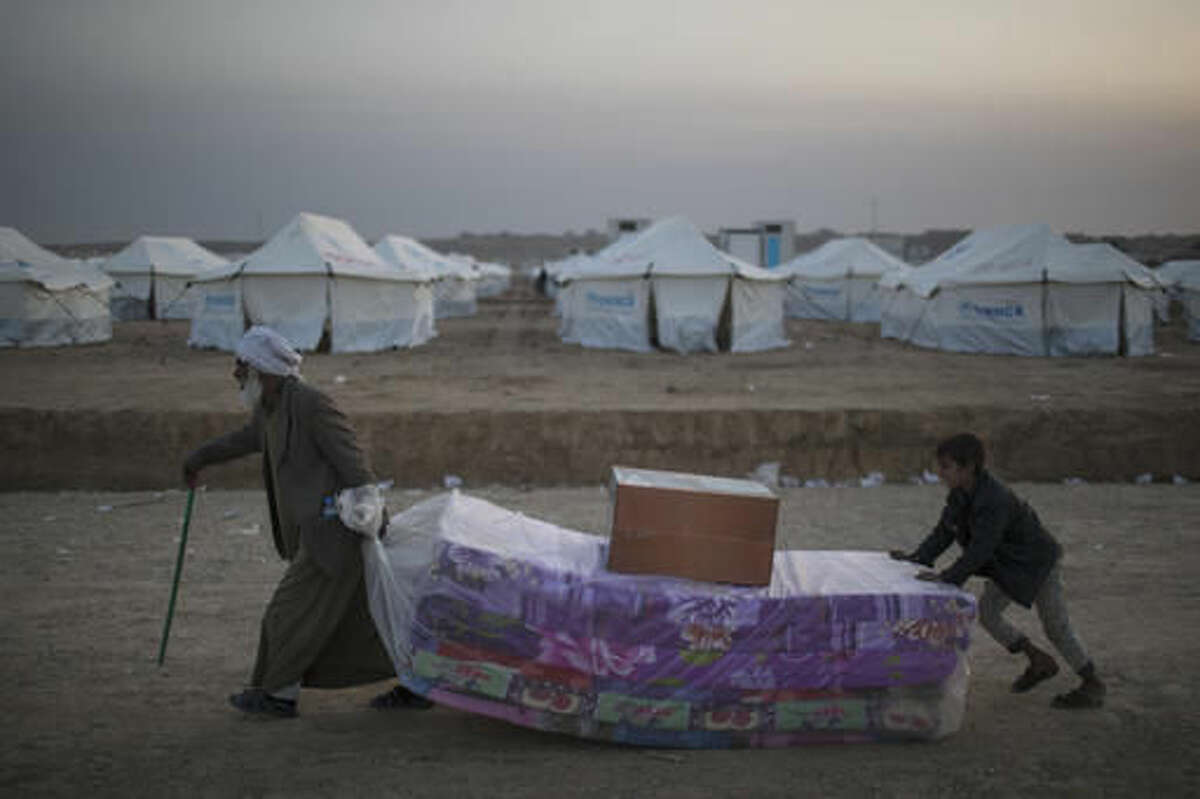 Iraqis displaced by fighting in Mosul carries mattresses at a camp for internally displaced people in Hassan Sham, Iraq, on Tuesday, Nov. 8, 2016. The United Nations says over 34,000 people have been displaced from Mosul, with about three quarters settled in camps and the rest in host communities. (AP Photo/Felipe Dana)