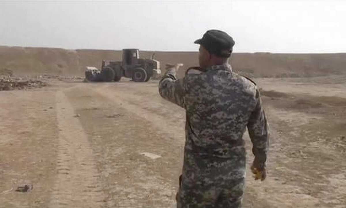 In this Monday, Nov. 7, 2016 frame grab from video, an Iraqi federal police officer walks towards a mass grave in Hamam al-Alil, Iraq. The Iraqi military says it has found some 100 decapitated bodies in a mass grave south of the Islamic State-held city of Mosul. According to the spokesman for the Joint Military Command, Brigadier General Yahya Rasool, the bodies were discovered on Monday near the agricultural college in the town of Hamam al-Alil. (AP Photo)