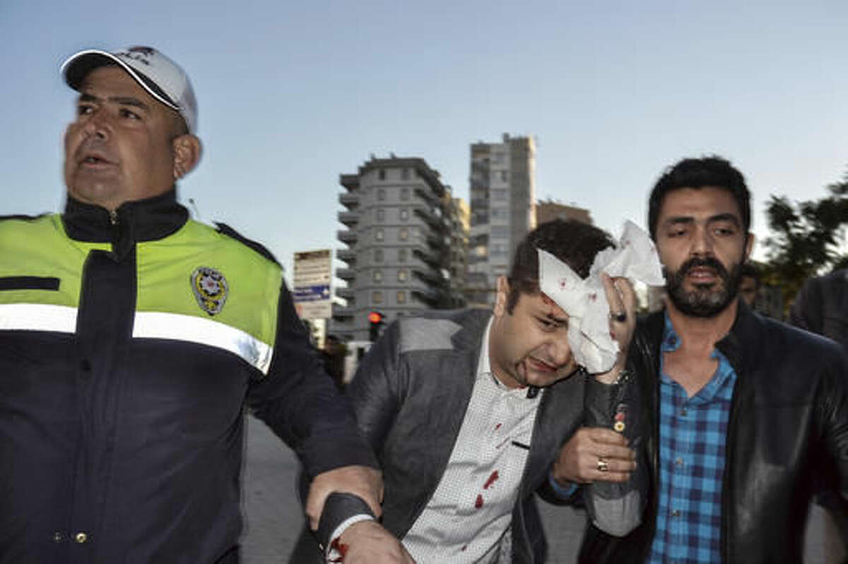 A police officer and a civilian help a wounded person after an explosion that killed people and wounded several others in southern city of Adana, Turkey, Thursday, Nov. 24, 2016. The explosion occurred early Thursday in the car park of a government building, officials said. Turkish authorities have banned distribution of images relating to the Adana explosion within Turkey. (AP Photo)
