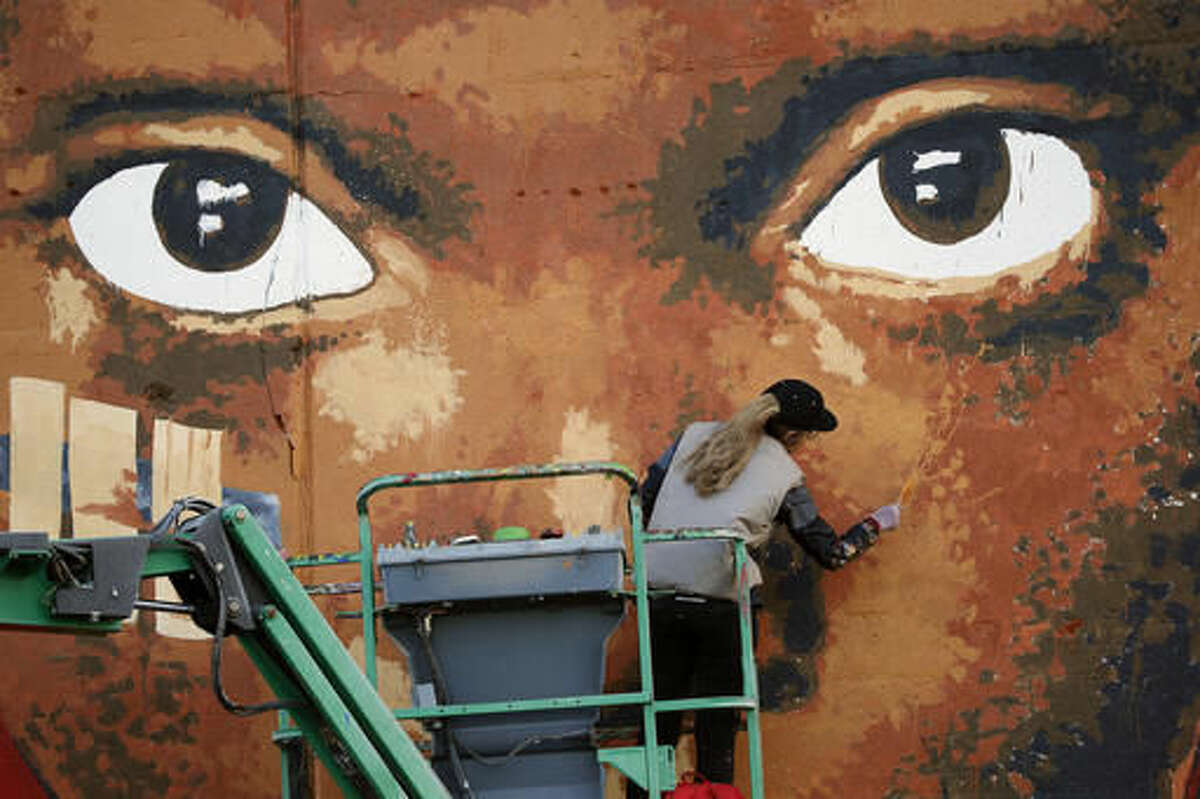 In this Sept. 25, 2016 photo, Brazilian artist Ananda Nahu works on the mural she created on over more than 600 feet of wall at Lakeview Terrace Estates, in Cleveland. Nahu was struck by the underlying strength of black culture there and the vulnerability of the children. She decided to paint a few of them on the wall, with some of them surrounded by patterns meant to reflect protection and majesty. (Gus Chan/The Plain Dealer via AP)