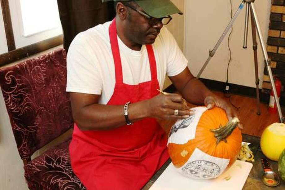 In this Oct. 24, 2016 photo, Fruit carver Lincoln Bias carves a pumpkin with a pattern attached in Rockford, Ill. Bias is an artist, a sculptor, of sorts, whose artwork only remains in photographs and in the memories of the people who are lucky enough to catch a glimpse. Bias, who has lived off and on in Rockford for the past 10 years, carves his masterpieces in fruit, vegetables, garnishes and even soap. (Maggie Hradecky/Rockford Register Star via AP) Photo: Maggie Hradecky