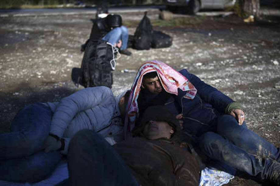 Syrian refugees wait to be picked up by the police on the outskirts of the northern Greek city of Thessaloniki, on Wednesday, Nov. 30, 2016. Authorities in Greece say they have picked up about 70 migrants, including children, found in the forested area after a truck driver left them and they spent the night there in the snow. (AP Photo/Giannis Papanikos) Photo: Giannis Papanikos