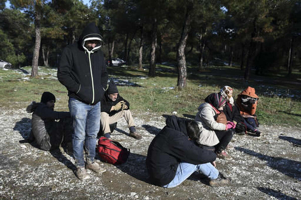 Syrian refugees wait to be picked up by the police on the outskirts of the northern Greek city of Thessaloniki, on Wednesday, Nov. 30, 2016.Authorities in Greece say they have picked up about 70 migrants, including children, found in the forested area after a truck driver left them and they spent the night in the snow. (AP Photo/Giannis Papanikos)