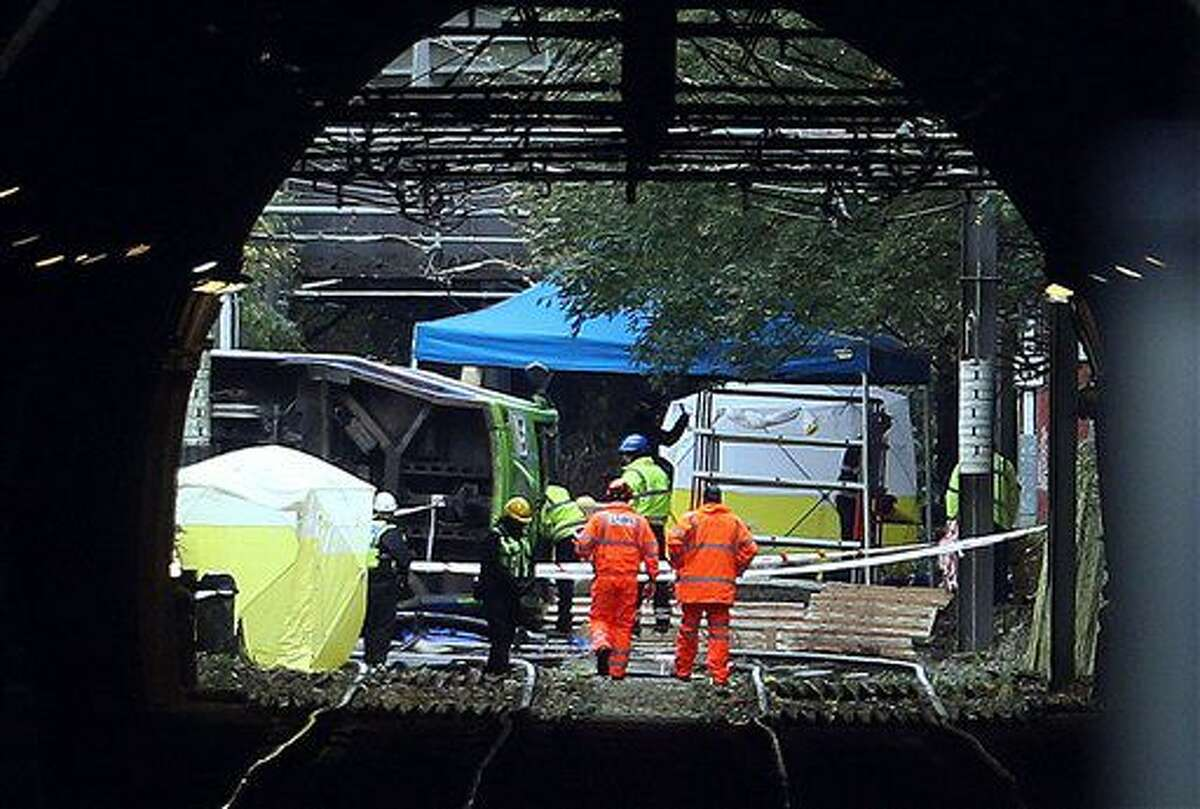 Work continues at the scene where tram derailed killing a number of people in Croydon south London Thursday Nov. 10, 2016 . The tram derailed while rounding a tight curve in a rainstorm in south London Wednesday, police said. (Steve Parsons/PA via AP)