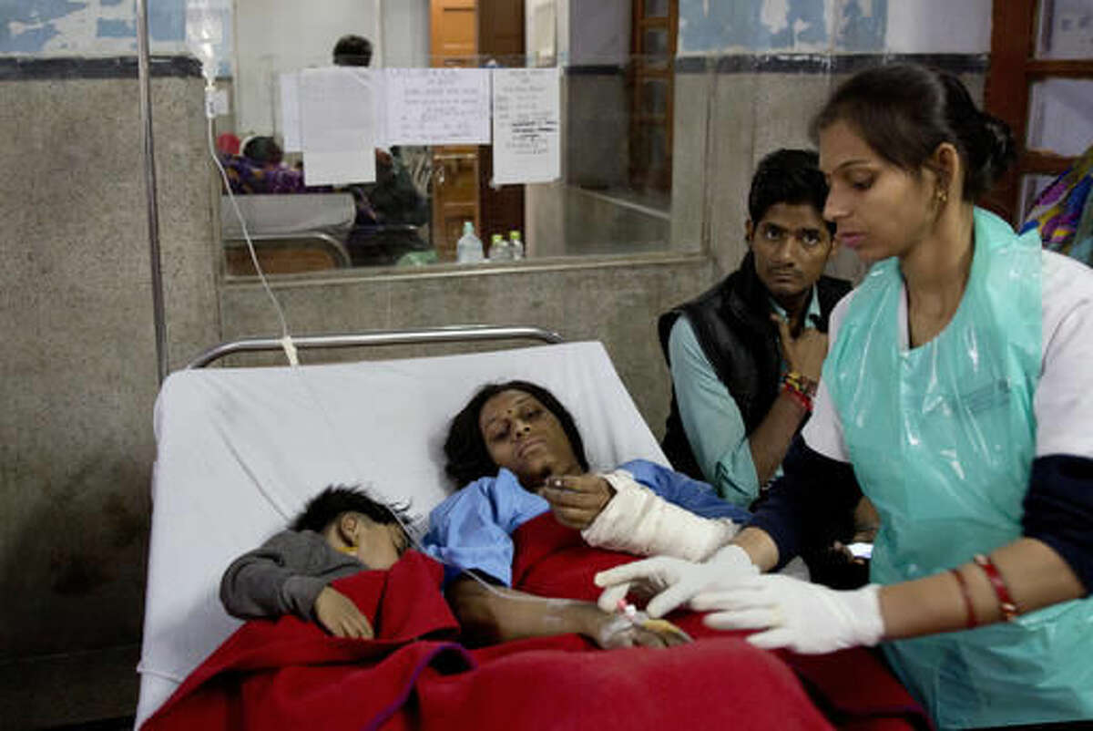 An injured passenger and her son share a bed as they are treated at a hospital in Kanpur, in the northern Indian state of Uttar Pradesh, India, Monday, Nov. 21, 2016. Scores of passengers died and scores more were injured after 14 coaches of an overnight passenger train rolled off the track near Pukhrayan village in Kanpur Dehat district. (AP Photo/Rajesh Kumar Singh)