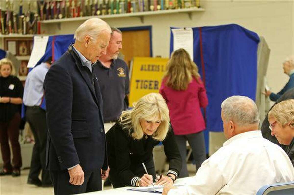 Vice President Joe Biden watches as his wife Jill Biden signs the voters register before voting Tuesday, Nov. 8, 2016, at A.I. DuPont High School in Wilmington, Del. (Jennifer Corbett/The Wilmington News-Journal via AP)