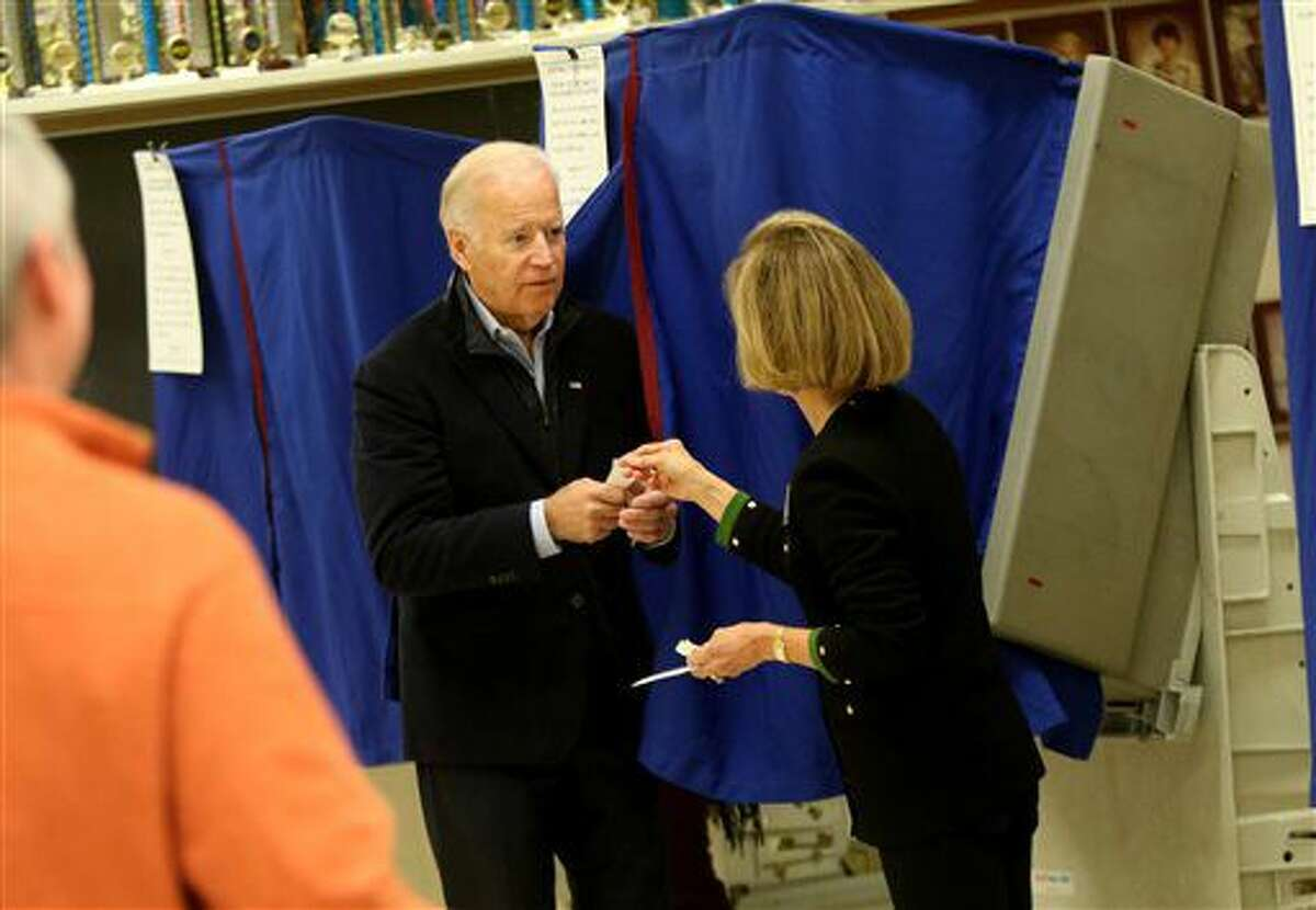 """Vice President Joe Biden receives his """"I Voted"""" sticker after casting his vote on Election Day on Tuesday, Nov. 8, 2016, at A.I. DuPont High School in Wilmington, Del. (Jennifer Corbett/The Wilmington News-Journal via AP)"""