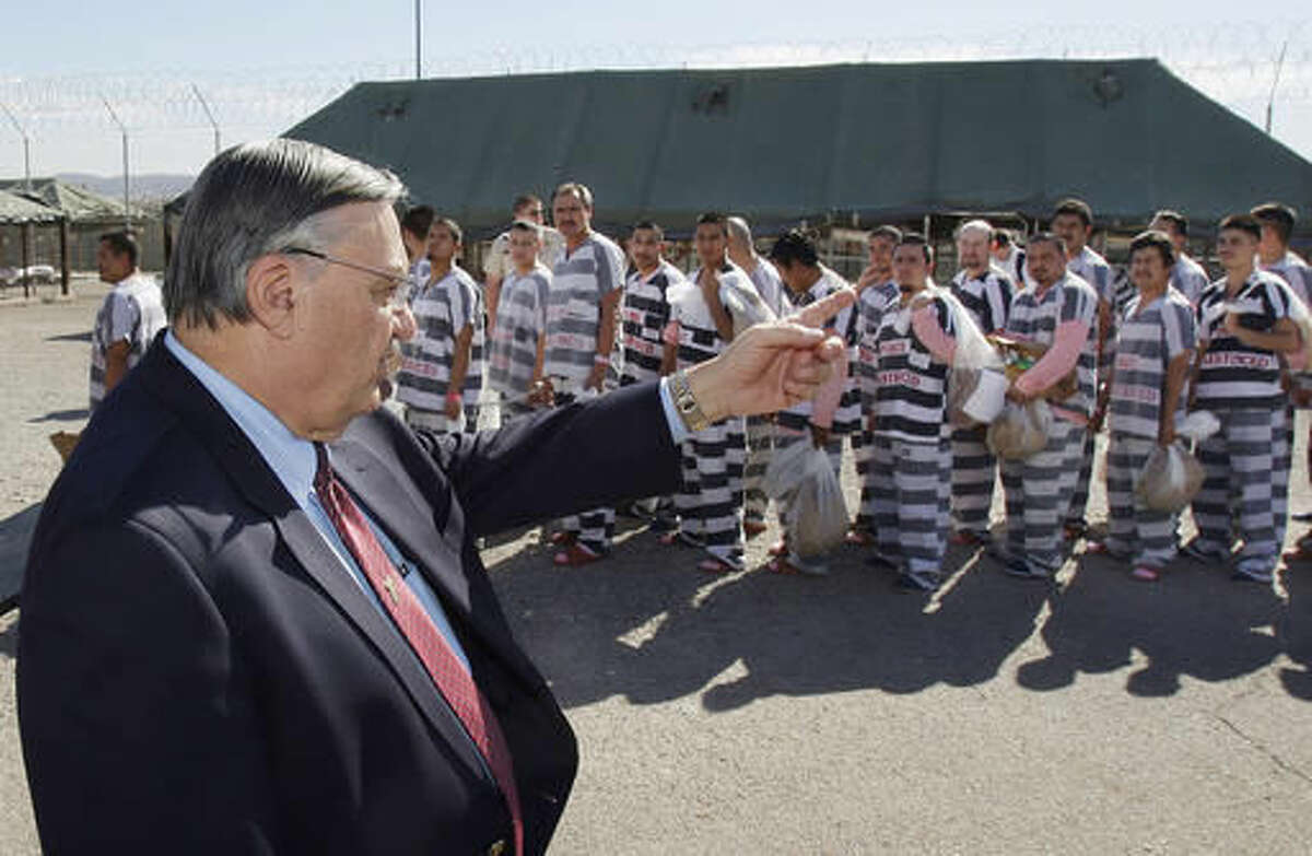 FILE - In this Feb. 4, 2009 file photo, Maricopa County Sheriff Joe Arpaio, left, orders approximately 200 convicted illegal immigrants handcuffed together and moved into a separate area of Tent City, for incarceration until their sentences are served and they are deported to their home countries, in Phoenix. Arpaio became a national political figure by taking on duties that none of his counterparts would ever touch, jailing inmates in tents, making them wear pink underwear, leading immigration crackdowns and investigating President Barack Obama's birth certificate. The defeat of the longtime sheriff of metro Phoenix raises questions about whether his successor, Paul Penzone, will keep the contentious practices and how he will overhaul an agency that has been criticized for targeting immigrants, creating a culture of cruelty in its jails and serving as self-promotional vehicle for Arpaio. (AP Photo/Ross D. Franklin, File)