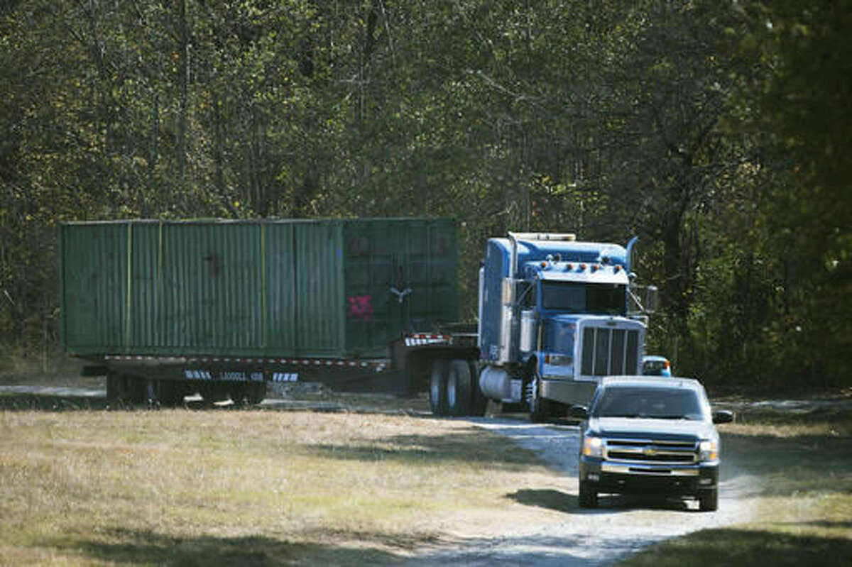 The shipping container that an abducted woman was held in for two months is removed from Todd Kohlhepp's property in Woodruff, SC., on Wednesday, Nov. 9, 2016. The property owner, Todd Kohlhepp, was arrested at his suburban home in Moore when investigators searching the property discovered the woman alive and chained in the large storage container, yelling for help. After Kohlhepp's arrest, deputies say he confessed to killing four other people in the county at a motorcycle shop in 2003. (Lauren Petracca/The Greenville News via AP)