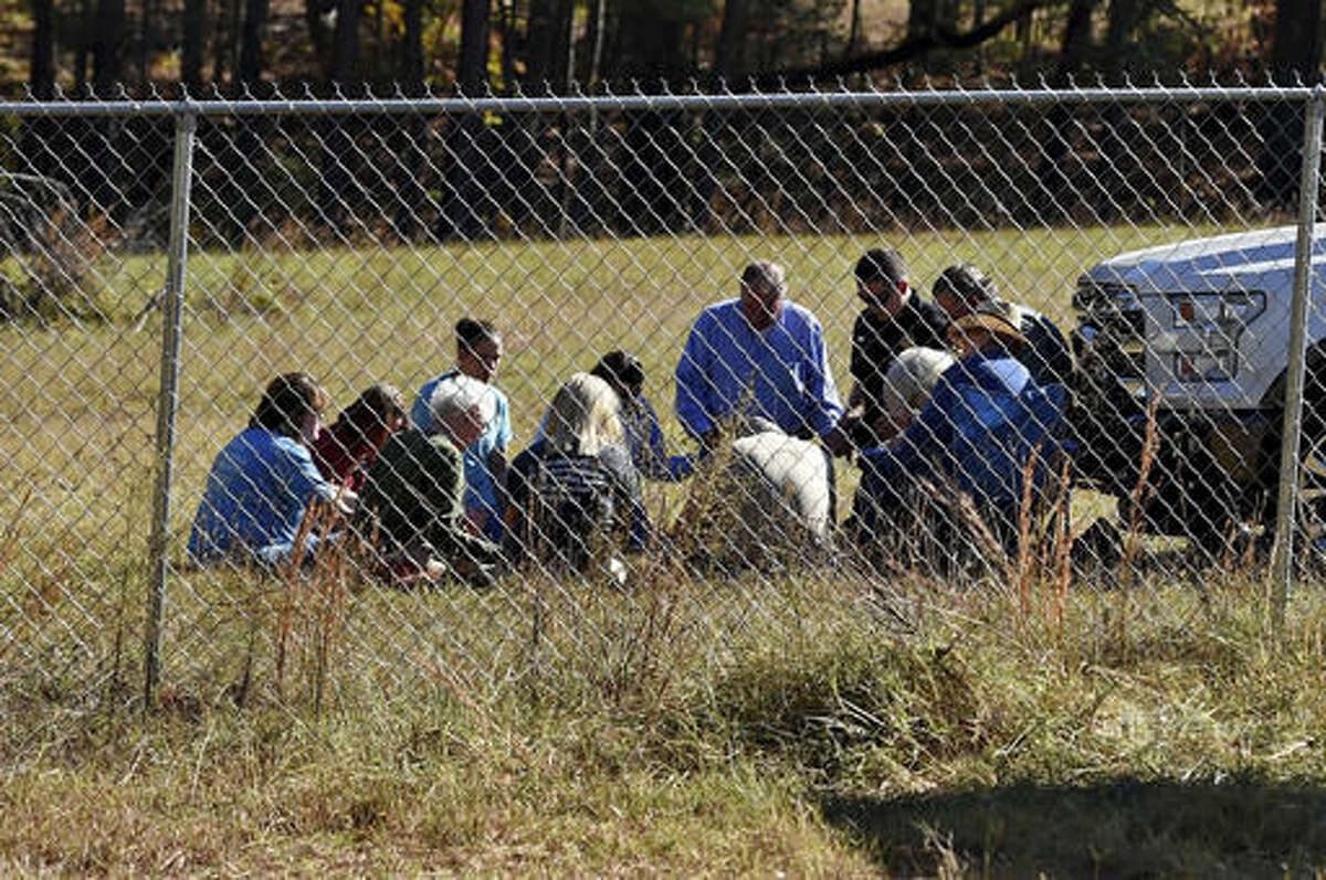 Duncan First Baptist church members,with South Carolina State Rep. Bill Chumley, hold a prayer service on Todd Kohlhepp's property in Woodruff, S.C. Monday, Nov. 7, 2016. Kohlhepp was arrested for kidnapping a woman and keeping her in a storage container on his property. He is also charged with four counts of murder at Superbike Motorsports in Chesnee, S.C. in 2003. (AP Photo/Richard Shiro)