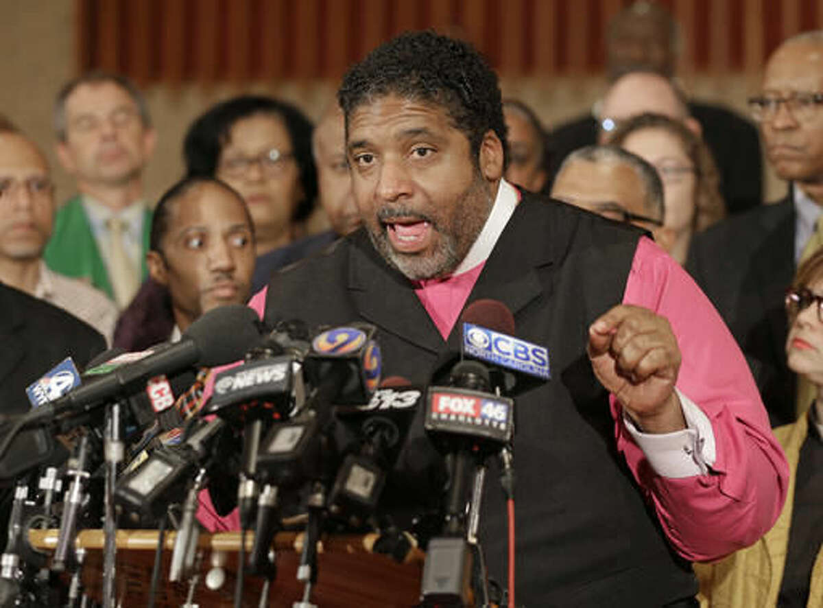 """FILE - In this Sept. 22, 2016, file photo, Rev. William Barber speaks during a news conference in Charlotte, N.C. Black clergy are taking to the pulpits and the streets nationwide in hopes of energizing black voters ahead of Election Day, aiming to make a difference in the presidential contest between Hillary Clinton and Donald Trump. """"Voting, for us, is both a spiritual and a political issue,"""" said Rev. William Barber, president of the North Carolina NAACP and architect of the Moral Monday Movement in North Carolina. (AP Photo/Chuck Burton, file)"""