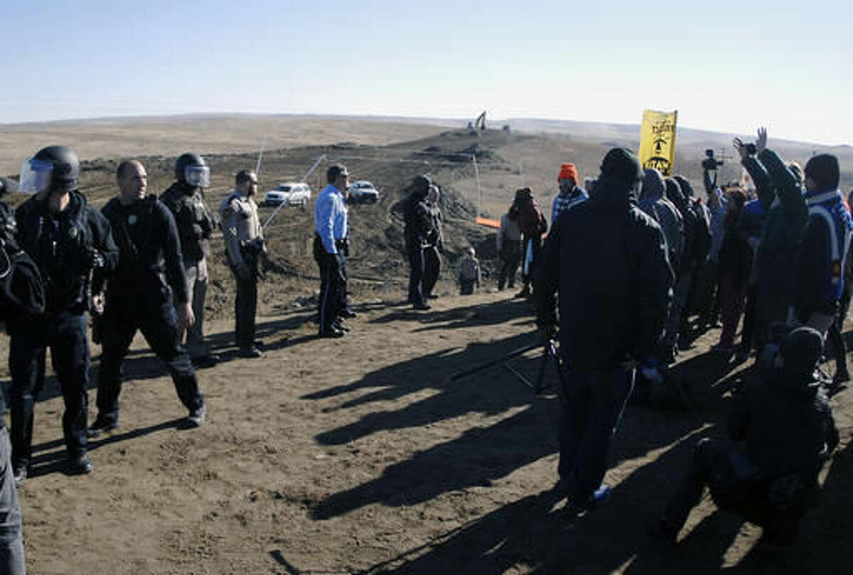 Law enforcement try to move Dakota Access Pipeline protesters further down during a protest at a pipeline construction site south of St. Anthony, N.D. Friday, Nov. 11, 2016. (Mike McCleary/The Bismarck Tribune via AP)